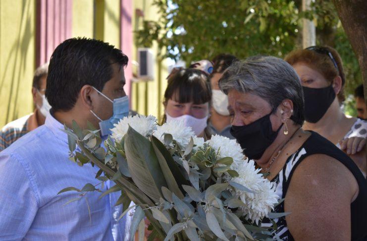 La madre de Nelson Lillo, Cristina, con la corona de flores que dispusieron en su memoria.