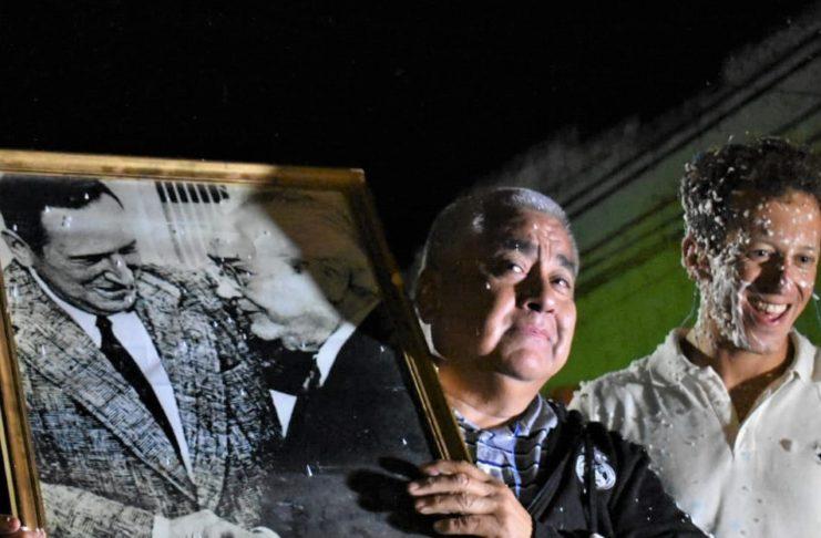 Salazar y Paz, en la celebración del triunfo electoral de 2019, con la foto del abrazo de Perón y Balbín.